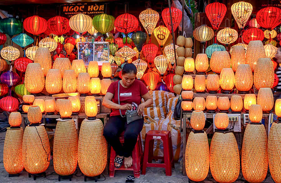 Nightmarket seller surrounded by colorful lanterns of all shapes and sizes hoping to pull in tourists wondering what to buy in Vietnam