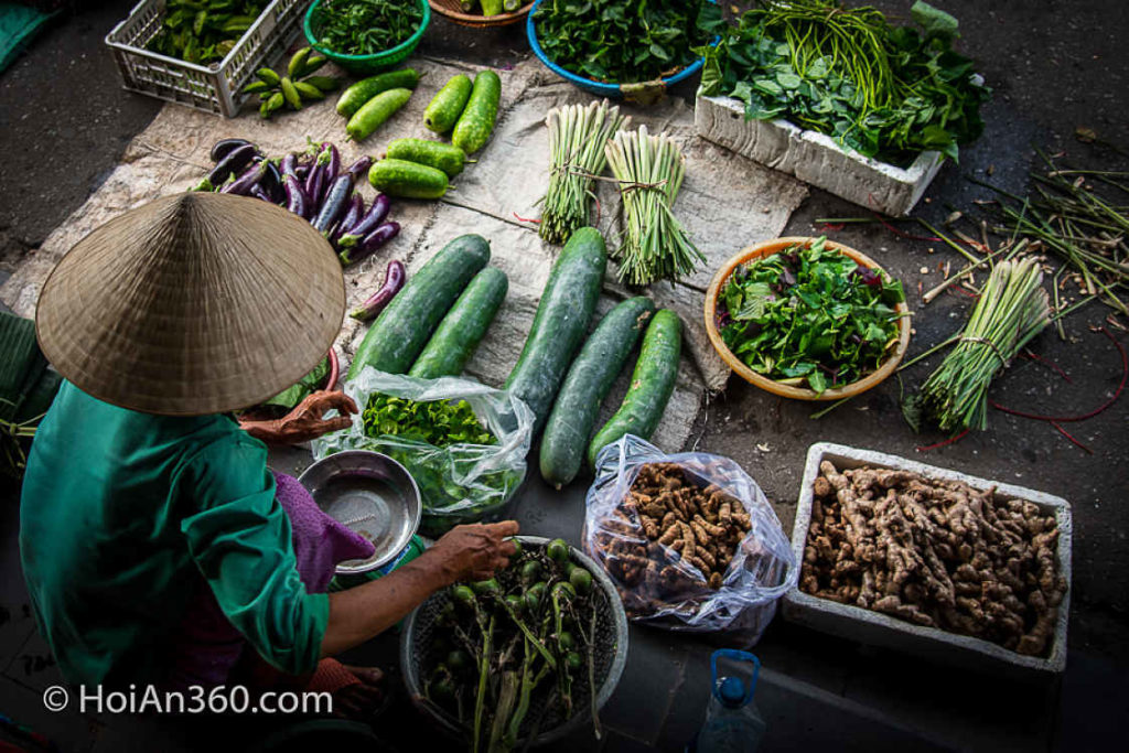 Aerial shot of Vietnamese seller in Conical hat selling green vegetables at Hoi An Market